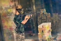 Videojugador femenino de Paintball en la acción Foto de archivo