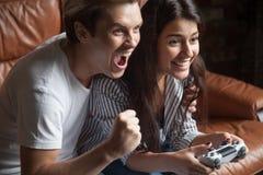 Videojugador femenino que juega al videojuego apoyado por el novio Foto de archivo