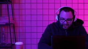 Videojugador joven alegre que juega a los videojuegos en casa en una corriente de funcionamiento del ordenador almacen de metraje de vídeo