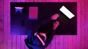 Videojugador profesional que juega al videojuego en su ordenador port?til Visualizaci?n blanca imagen de archivo libre de regalías