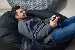 Videojugador que juega a los videojuegos con la palanca de mando que se sienta en silla del puf Imagenes de archivo