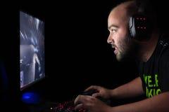 Videojugador que juega a una primera pistola de la persona en la PC de gama alta Imagen de archivo