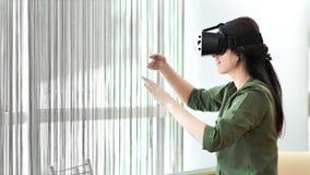 Videojugador tirado medio de la mujer que lleva los vidrios modernos de la realidad virtual que hacen las manos que agitan del ge metrajes