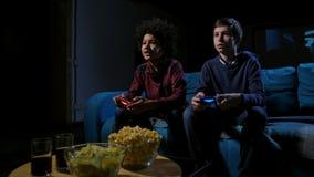 Videojugadores adolescentes concentrados que juegan la consola casera almacen de metraje de vídeo