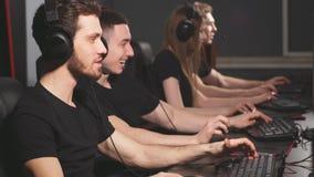 Videojugadores jovenes que juegan al videojuego mientras que pasa fin de semana en el club del juego de la PC almacen de video