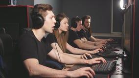 Videojugadores jovenes que juegan al videojuego mientras que pasa fin de semana en el club del juego de la PC metrajes