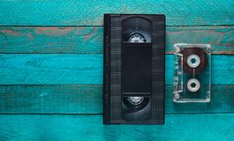 Videokassett, ljudkassett på turkosen trätabell Retro massmediateknologi från 80-tal kopiera avstånd Top beskådar Royaltyfri Foto