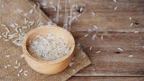 Videolengte van het gieten van ruwe bruine gehele korrelhalfwitte rijsten in houten kom op de doek van de jutezak op houten lijst stock videobeelden