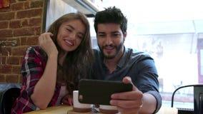 Videopn kalla Lyckliga par genom att använda telefonen för den videopd appellen i kafé arkivfilmer