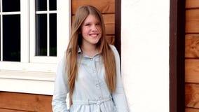 Videoporträt des jungen glücklichen lächelnden Mädchens auf dem Hintergrund ihres Hauses stock video
