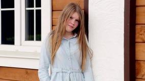 Videoporträt des jungen glücklichen lächelnden Mädchens auf dem Hintergrund ihres Hauses stock video footage
