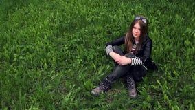 Videoporträt des lächelnden Sitzens des jungen Mädchens auf dem grünen Gras stock video footage