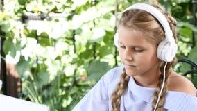 Videoportrait da menina adorável que senta-se na tabela com um caderno branco, pondo fones de ouvido sobre vídeos de arquivo