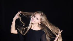 Videoportrait do modelo fêmea adorável do adolescente com o cabelo louro longo que levanta olhando a câmera Apropriado para comer video estoque