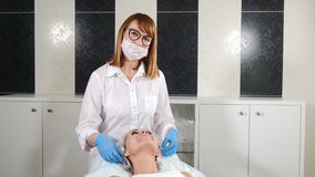 Videoportrait of happy friendly beautician smiling at camera. Middle-aged cosmetologist in white lab coat smiling while. Beauty procedure stock video