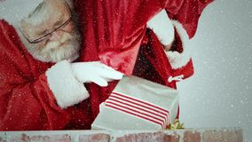 Videosamenstelling met dalende sneeuw over santa trowing giften binnen aan schoorsteen stock videobeelden