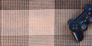 Videospelkontrollanten från den modiga konsolen är på den rutiga soffan Trådlös apparat för att kontrollera under videospelet Arkivbilder
