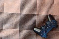 Videospelkontrollanten från den modiga konsolen är på den rutiga soffan Trådlös apparat för att kontrollera under videospelet Arkivbild