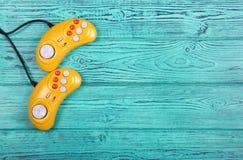 Videospelletjeconsole GamePad op een oude blauwe houten lijst als achtergrond Gele retro GamePad Royalty-vrije Stock Fotografie