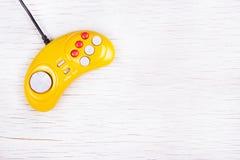 Videospelletjeconsole GamePad op een witte houten lijst Gele retro GamePad Stock Afbeeldingen