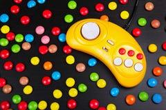 Videospelletjeconsole GamePad op een witte houten lijst Gele retro gamepad op een achtergrond van gekleurde chocoladedragees royalty-vrije stock afbeeldingen