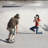 Videotaping skateboard action. Boy does tricks at the skateboard park as girl videotapes Royalty Free Stock Images