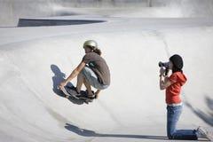 Videotaping skateboard action. Boy does tricks at the skateboard park as girl videotapes Stock Image