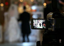 Videotaping the wedding. A video camera capturing a bride and groom at the altar of the church Stock Image