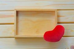 Videz la boîte en bois et le coeur rouge sur le fond en bois Image stock