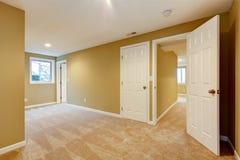 Videz la chambre à coucher neuve avec beaucoup de trappes et de tapis beige. Image stock