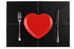 Videz la fourchette rouge de couteau de plaque de coeur sur le cuir noir Photo stock