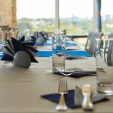 Videz la table de banquet moitié-servie dans le restaurant avec des serviettes, verres, fourchettes, les couteaux, vue peu profon Images libres de droits