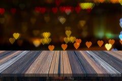 Videz la table ou la planche en bois avec le bokeh d'amour de coeur de la lumière de la route ou de la rue avec la tour de ville  Photos stock