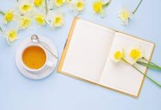 Videz la tasse ouverte de carnet de thé et les jonquilles jaunes sur le fond bleu-clair Configuration d'appartement de vue supéri Photographie stock