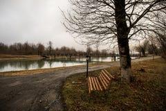 Videz le banc au parc près de l'étang par jour brumeux, scène froide minimalistic de saison banc au lac dans le brouillard dans l Image stock