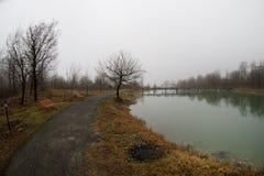 Videz le banc au parc près de l'étang par jour brumeux, scène froide minimalistic de saison banc au lac dans le brouillard dans l Image libre de droits
