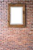 Videz le cadre de tableau en bois accrochant sur un mur de briques Photographie stock