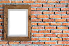 Videz le cadre de tableau en bois accrochant sur un mur de briques Images stock