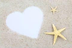 Videz le coeur et les étoiles de mer blancs sur la plage Photo libre de droits