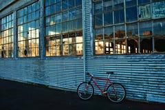 Videz le vieil entrepôt avec le verre cassé, vélo se penchant sur le mur photos libres de droits