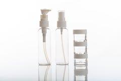 Videz les bouteilles et les pots transparents de cosmétiques sur le fond blanc images libres de droits