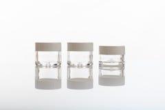 Videz les bouteilles et les pots transparents de cosmétiques sur le fond blanc photographie stock