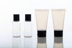 Videz les bouteilles et les pots transparents de cosmétiques sur le fond blanc images stock