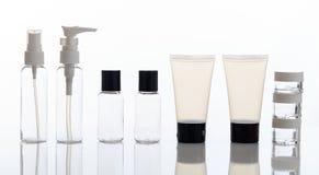 Videz les bouteilles et les pots transparents de cosmétiques sur le fond blanc photo stock
