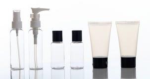 Videz les bouteilles et les tubes transparents de cosmétiques sur le fond blanc photographie stock libre de droits
