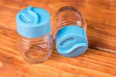 Videz les nouveaux dispositifs trembleurs de sel et de poivre sur le conseil en bois Photographie stock