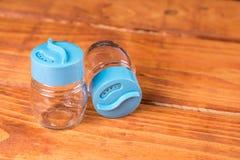 Videz les nouveaux dispositifs trembleurs de sel et de poivre sur le conseil en bois Photo stock