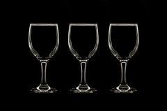 Videz trois verres de vin sur le fond noir Photos libres de droits