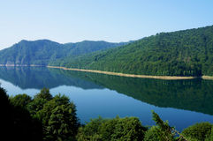 The Vidraru lake in Fagaras mountains of Romania. Panorama view of the Vidraru lake in Fagaras mountains of Romania with black swallows flying over the water royalty free stock photography