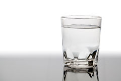 Vidrio aislado de agua en la tabla con la reflexión Imágenes de archivo libres de regalías